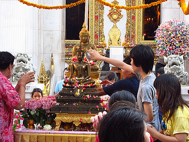 Visiting a temple during Songkran and pouring water on the statue of the Buddha