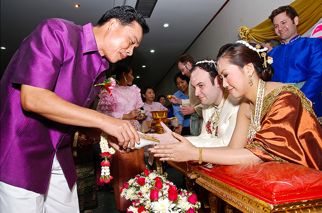 An elder relative pours water from a conch shell over the hands of the bride and groom during a wedding ceremony