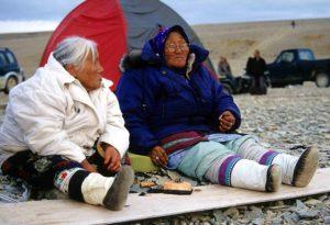 Inuit women eating maktaaq, whale skin