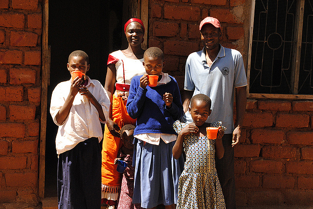 A couple generations of a Tanzanian farm family, Elizabeth Azaria, her husband, and their three children in front of her home in the Iramba District