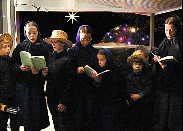 The Amish tend to idealize the lives of their children, shown here singing Christmas carols