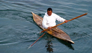 An Inuit hunter in a traditional kayak and carrying a harpoon (Photo by Ville Miettinen on Flickr, Creative Commons license)