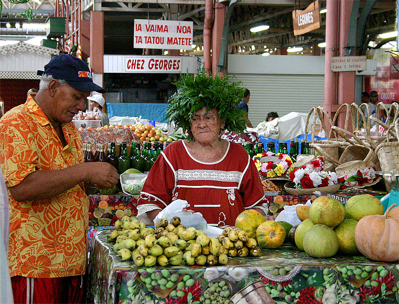 """Image of two older Tahitians at the municipal market in Papeete; the photographer only says about the lady's unusual hat, """"The intersection of Gallic flair and local flora?"""""""