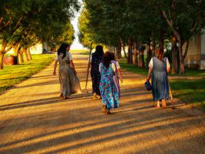 Hutterite women wear modest dresses in the light of a South Dakota sunset