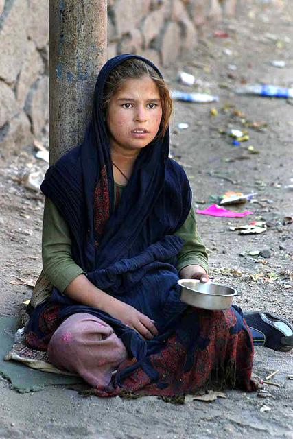 A poor Ladakhi girl begging in a trash-lined street (Photo by Steve Evans on Flickr, Creative Commons license)