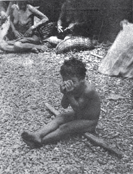 An Ifaluk child playing peek-a-boo with the photographer
