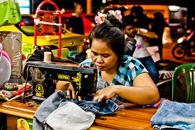 A seamstress repairs a pair of jeans at her streetside sewing stand in Bangkok
