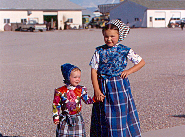 Two Hutterite girls with farm buildings in the background at the Milford Colony in Montana, a branch of the Milford Colony in Alberta (Photo by Roger W on Flickr, Creative Commons license)