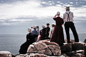 A group of Amish people look out to sea at Acadia National Park on the coast of Maine