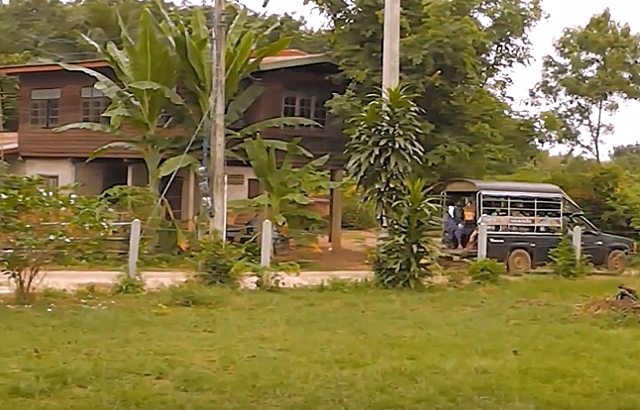An old school bus passing through a village in Isan