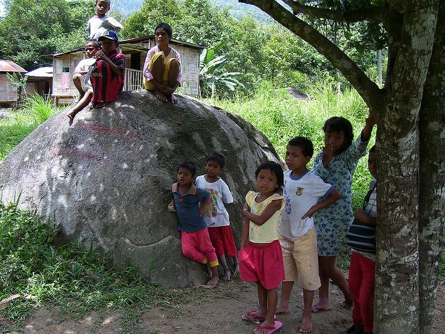Some Semai children gathered around a big rock