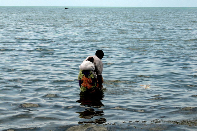 A woman with her baby washing laundry in Lake Tanganyika