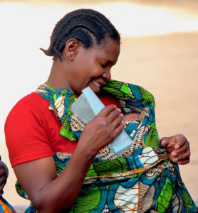 A woman waiting with her baby at the Mtowisa Health Center in the Rukwa Region (Photo by Katy Woods for The White Ribbon Alliance was on Flickr with a Creative Commons license)++