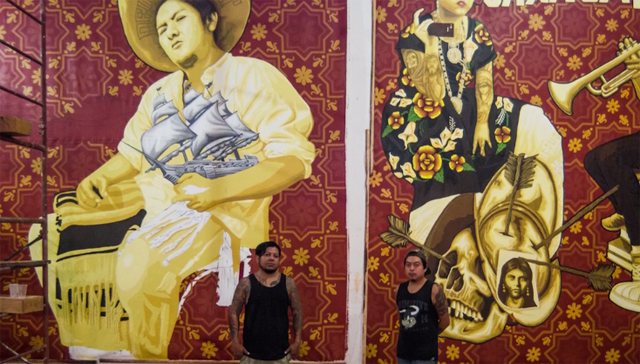 The Zapotec artists Dario Canul and Cosijoesa Cernas standing in front of their murals